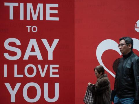 Los peatones pasando junto a un recorte del Día de San Valentín que se muestra fuera de un centro comercial en Hong Kong.