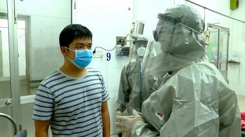 Vietnam's vice minister of health, Nguyen Truong Son, talks with a man at an isolated section of a hospital where two Chinese citizens had tested positive for coronavirus, in Ho Chi Minh city.