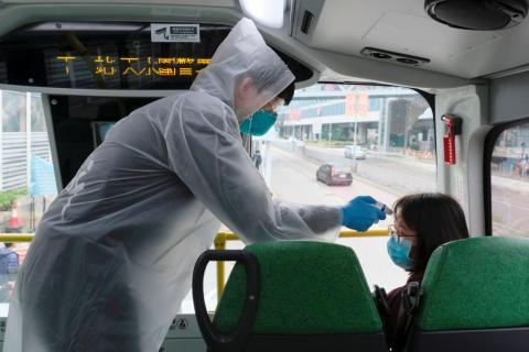 A resident wearing mask and raincoat takes the temperature of passenger at a bus stop at Tin Shui Wai, China, February 4, 2020.