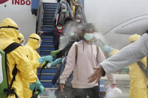Indonesios llegando desde Wuhan, China, siendo rociados con antiséptico en el aeropuerto Hang Nadim en Batam el 2 de febrero.