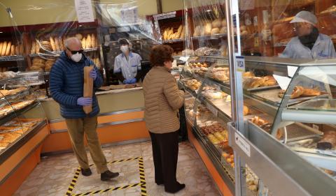 2 clientes con mascarilla compran pan en una panadería de Madrid