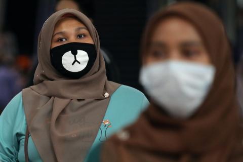 2 mujeres con mascarillas en una estación de Kuala Lumpur (Malasia)