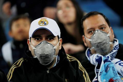 Aficionados ven el partido del Real Madrid con mascarilla ante el miedo por el brote del coronavirus