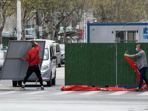 Trabajadores con mascarillas eliminan las barreras en una calle de Wuhan el 21 de marzo de 2020.