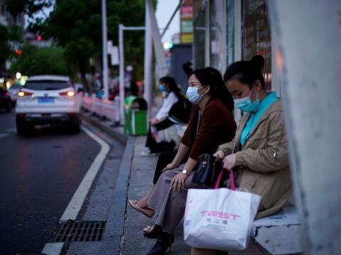 Estas mujeres esperan al autobús en una parada en Xianning, el 25 de marzo de 2020.