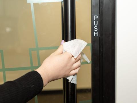 Put a barrier in between your hand and the door handle.
