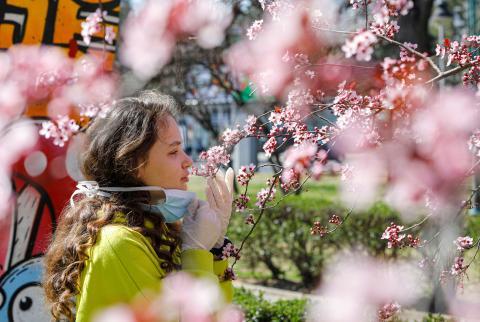 Una chica huele flores en medio de la pandemia del coronavirus