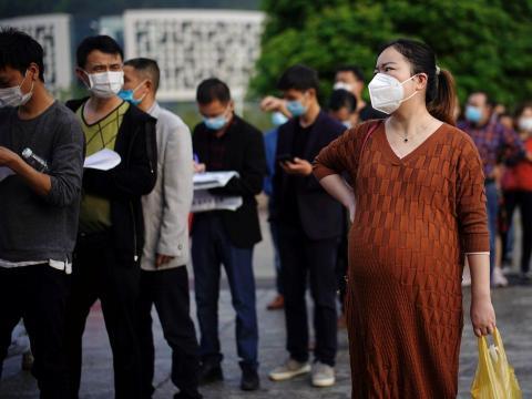 Las personas que usan mascarillas se alinean frente al Hospital Central de Xianning el 26 de marzo de 2020.