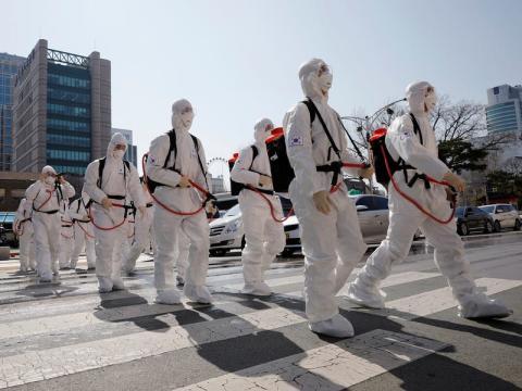 Soldados surcoreanos con equipo de protección caminan en una calle frente al ayuntamiento de Daegu después del rápido aumento de los casos confirmados de coronavirus el 2 de marzo de 2020.