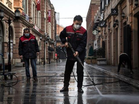 Cleaners wash a street in the quarantined city of Wuhan with a high-pressure water gun on February 3, 2020.