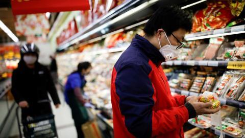 Un cliente con máscara compra comida durante el brote de coronavirus.
