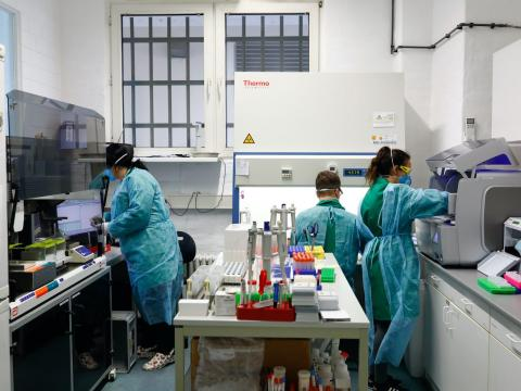 Employees in protective clothing do testing for the coronavirus at a laboratory in Berlin, Germany, March 26, 2020.