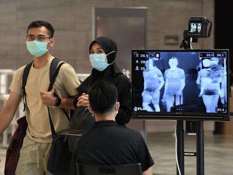 Una pareja pasa un control de temperatura en el aeropuerto internacional de Changi en Singapur el 27 de febrero de 2020.