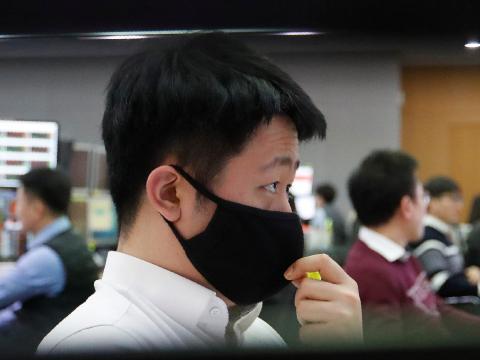 Un comerciante de divisas con una mascarilla observa los monitores en la sala de comercio de divisas.