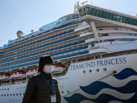 Un miembro de los medios de comunicación pasa junto al crucero Diamond Princess en el muelle Daikoku en Yokohama, Japón, el 2 de febrero de 2020.