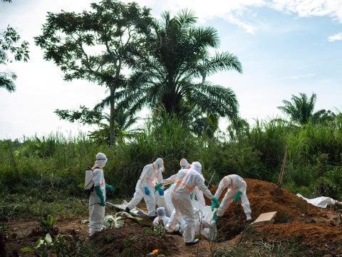 Workers burying the body of an Ebola victim.