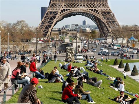 Parisinos y  turistas se relajan en la hierba cerca de la Torre Eiffel.