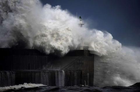Enormes olas se estrellan contra un puerto marítimo, al norte de España.