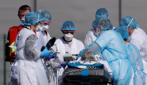Un equipo médico francés prepara a un paciente con coronavirus para su traslado a Alemania en el aeródromo militar de Mulhouse (Francia)