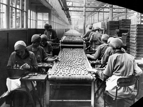Mujeres glaseando galletas en una fábrica.
