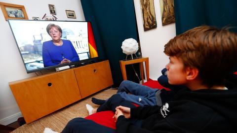 Una familia alemana ve a Angela Merkel por la tele.