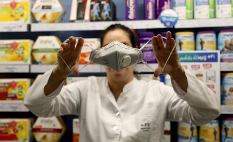 Una farmacéutica de Barcelona sujeta una mascarilla