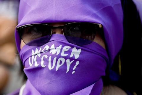 Una mujer filipina se cubre la cara con un paño mientras se une a un flash mob para ocupar una calle en Manila, Filipinas.
