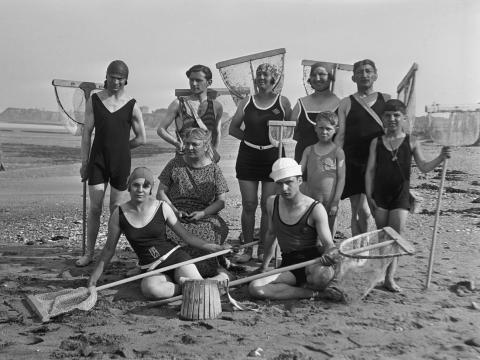 Una gran familia de hombres, mujeres y niños, todos con redes de camarones en una playa de Alemania, alrededor de 1920.