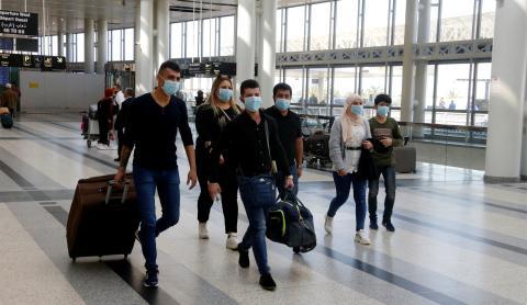 Un grupo de pasajeros con mascarilla busca su puerta de embarque en el aeropuerto de Beirut