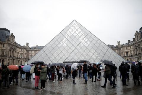 Grupos de turistas se agolpan en la entrada del Museo del Louvre de París (Francia)