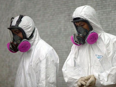Health workers wear full protective clothing during a clean up operation at Amoy Gardens in Hong Kong, where over 200 residents were infected with SARS, April 4, 2003.