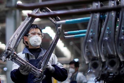 Un hombre con mascarilla para el coronavirus en una fábrica.