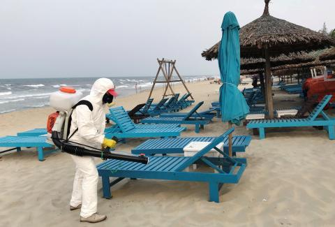 Un hombre con traje de protección desinfecta unas tumbonas de playa por el coronavirus.