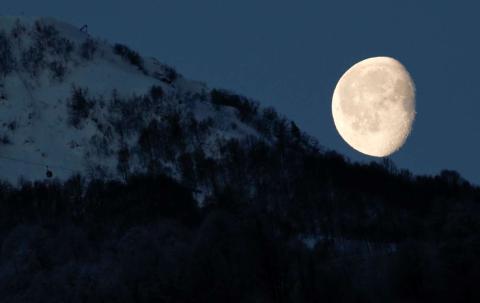 La luna se asoma por encima de las montañas en Rosa Khutor, Rusia, durante los Juegos Olímpicos de Sochi 2014.
