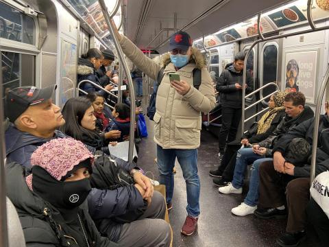 Un hombre con una mascarilla viaja en el metro.
