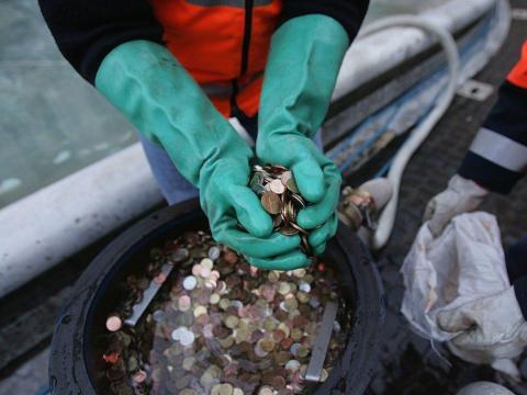 Un hombre tiene monedas recogidas de la Fontana de Trevi en Roma, Italia.