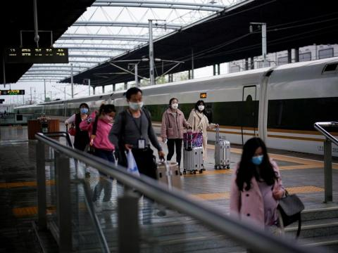 Pasajeros que llevan mascarillas viajan con sus maletas en una estación de tren en Xianning, provincia de Hubei, el 25 de marzo de 2020.