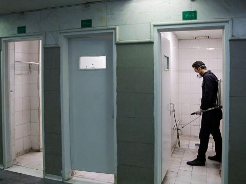 A member of a medical team sprays disinfectant to sanitize bathrooms in Imam Reza's holy shrine in Mashhad, Iran, on February 27, 2020.