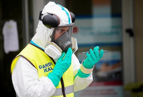 Un miembro de la guardia real sujeta un movil con un equipo de protección contra el coronavirus