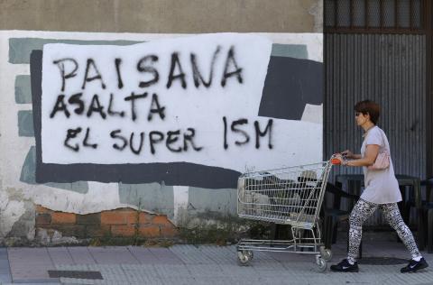 Una mujer camina con un carrito al lado de un mural cerca de Oviedo.