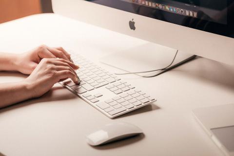 Mujer escribiendo en un teclado de Apple
