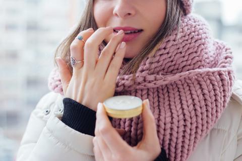 Una mujer hidratando sus labios.