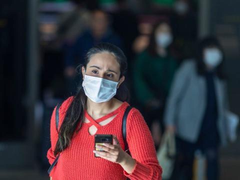 Turista con mascarilla en el aeropuerto internacional de Los Ángeles. Ella no es la mujer que fue puesta en cuarentena en San Diego.