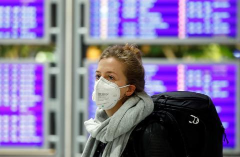 Una mujer con mascarilla por el coronavirus en un aeropuerto.