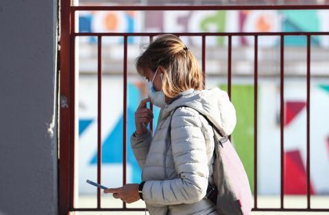 Una mujer con mascarilla a la salida de un colegio en Madrid.