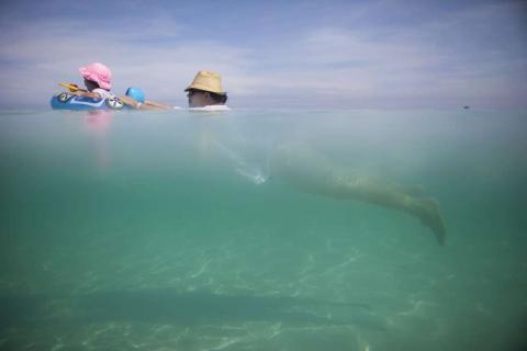 Una mujer nada en la playa con su nieta en Cuba.