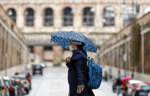 Una mujer pasea delante del Coliseo de Roma con una mascarilla en plena pandemia del coronavirus