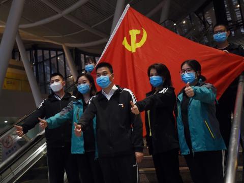 Trabajadores sanitarios de fuera de Wuhan posan para una fotografía con la bandera del partido comunista chino en la estación de tren de la capital de la región antes de rvolver a sus casas, el pasado 17 de marzo de 2020.