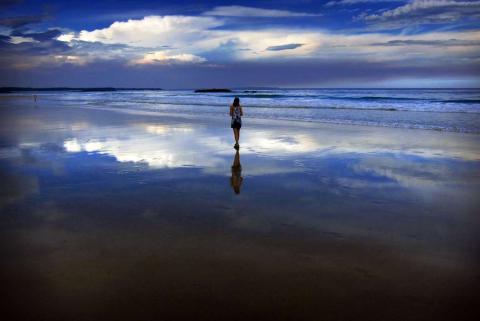 Nubes de tormenta y polvo por encima de una mujer que camina en la oscuridad, a lo largo de la Playa Mollymook, al sur de Sydney.