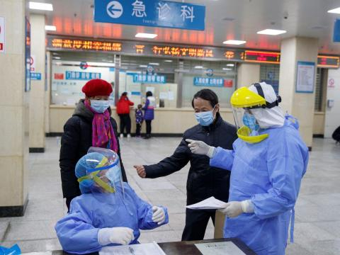 Nurses in protective gear talk to people in the reception area of the First People's Hospital in Yueyang, Hunan Province, China, January 28, 2020.